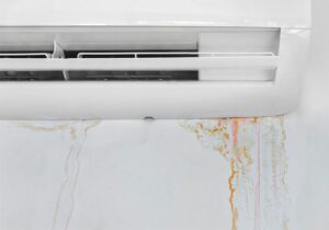 Wall with mold stain due to air conditioner leakage, close up. Mildew destroys the wall.