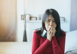 Woman suffering from indoor smoke and is coughing